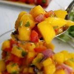 spicy mango salsa with spoon up close