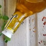 herb infused olive oil in bottle with herbs