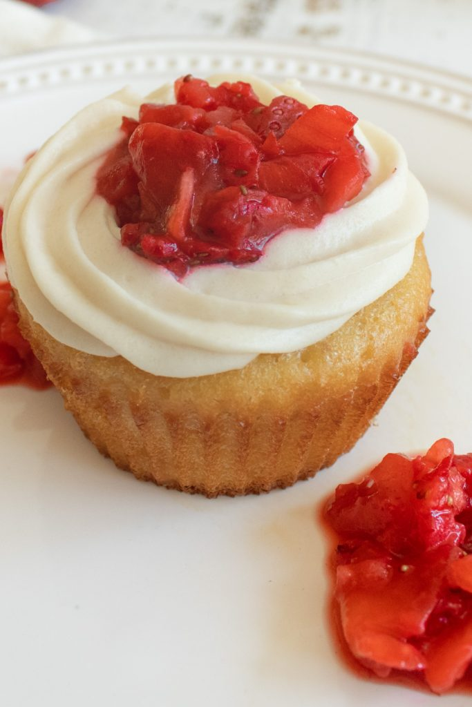 close up of strawberry cupcake with berries