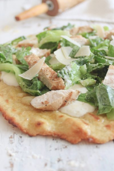 close angle shot of chicken salad caesar pizza