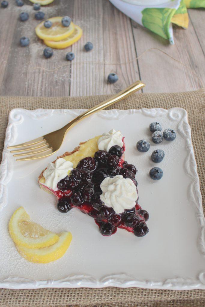 lemon curd tart with blueberries and lemon slice on plate