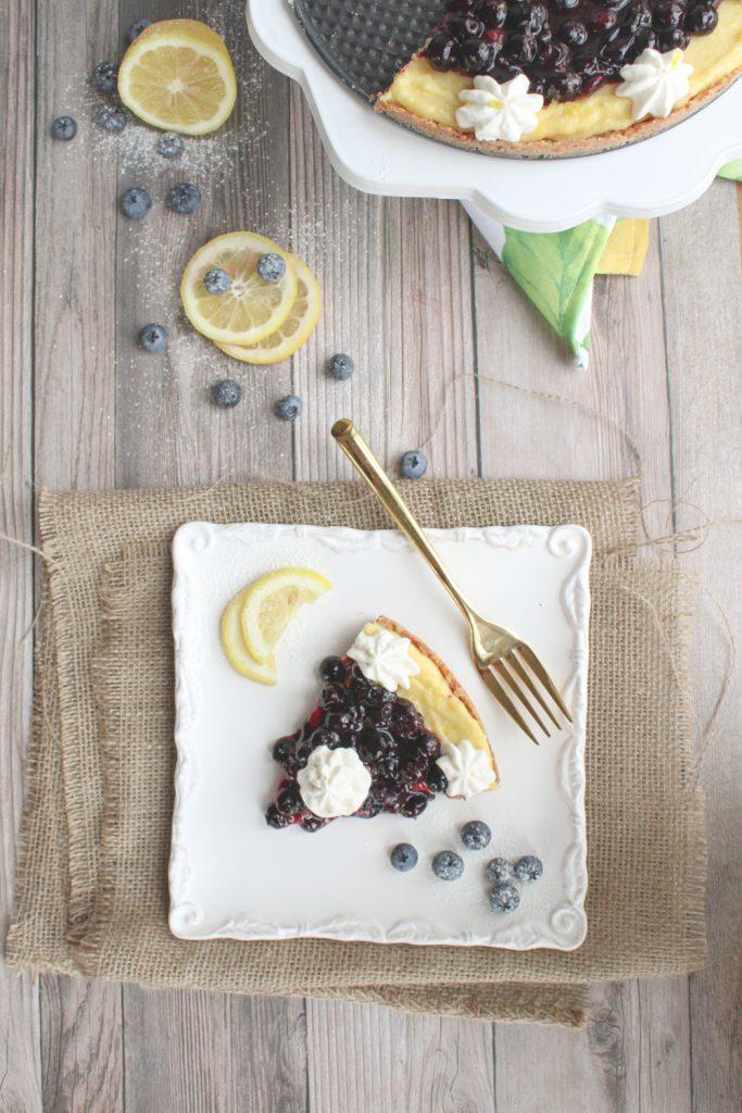 lemon curd tart on plate with blueberries and lemon slice