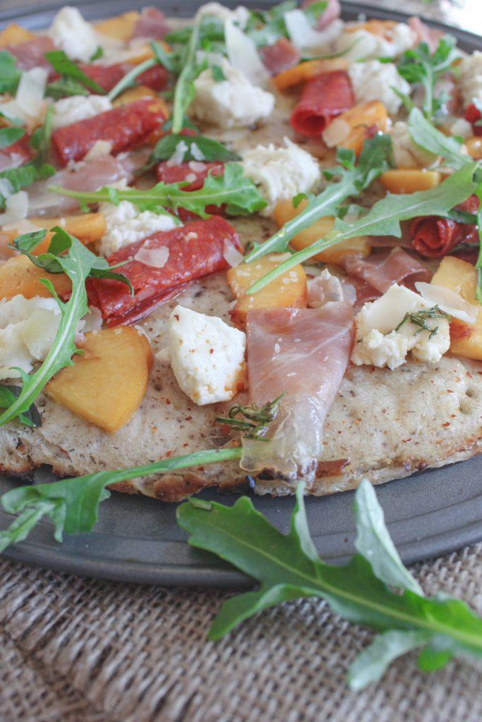 prosciutto pizza on tray with arugula