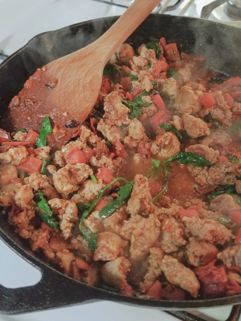 sausage, tomato and spinach cooking on stove