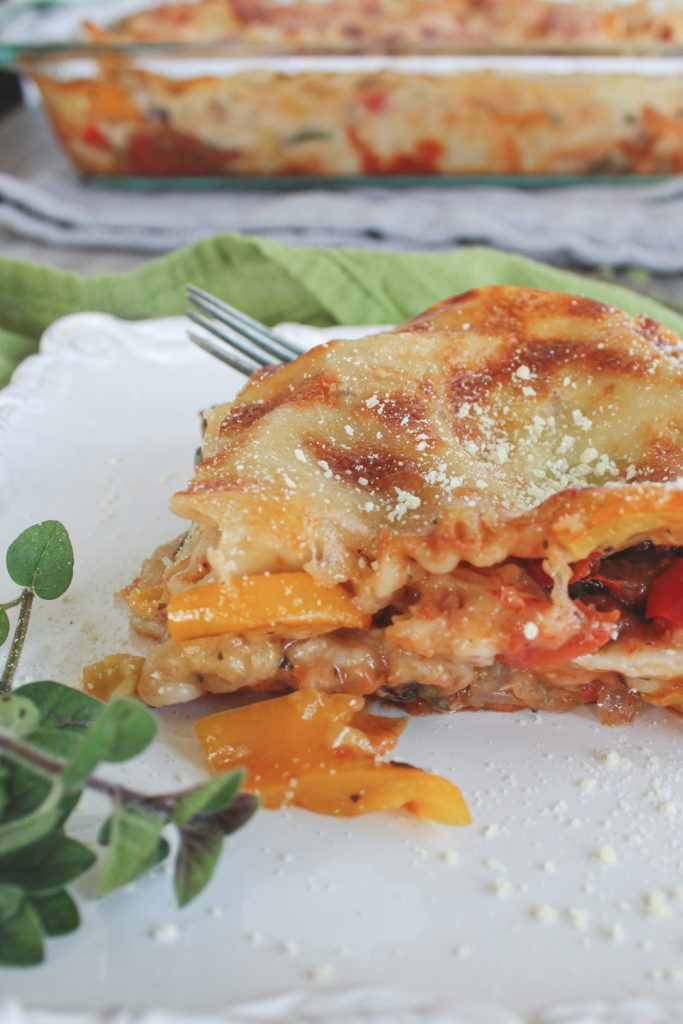 close up of vegetable lasagna in white sauce